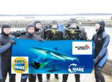 Divers holding giant Project AWARE certification card
